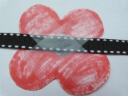 Tape poppy to the ribbon, string or rubber band that you're using