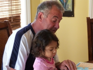 Toddler girls reading a story with her grandfather